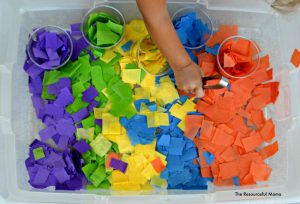 Using tongs to grasp pieces of tissue paper and sort into cups in this tissue paper sensory bin.