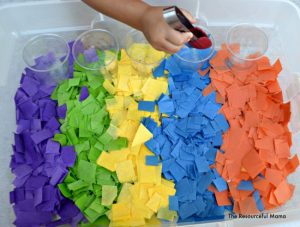 Using tongs to squeeze and grasp tissue paper and sort into cups with this tissue paper sensory bin.