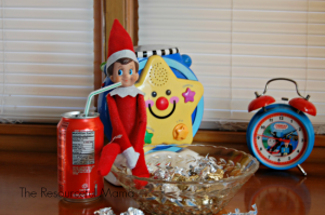 Elf on the Shelf drinking a coke and snacking on heresy kisses