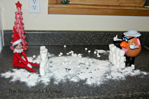 Elf on the Shelf having a snow ball fight with Mr. Potato Head