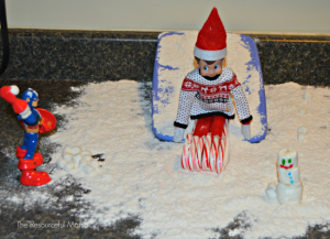 The Elf on the Shelf is playing in the snow.
