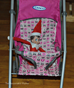 The Elf on the Shelf in the baby doll stroller.