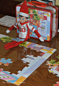 The Elf on the Shelf doing a puzzle.