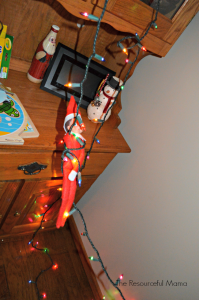 Elf on the Shelf dangling from Christmas lights